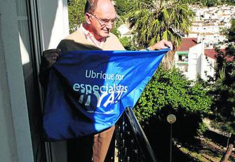 El portavoz del movimiento Especialistas Ya, retirando, ayer, una de las banderas reivindicativas.